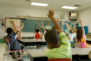 classroom with students raising hands